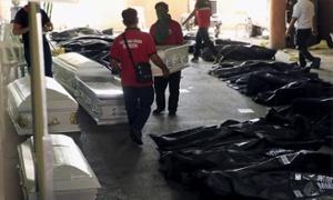 ○ヴァレンズエラ市ホールで、工場火災の遺体バッグそばに棺桶を運んでいる.jpg