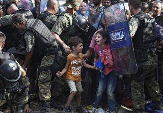 ギリシャに上陸したシリア難民、ギリシャ警察に押しとどめられる (320x222).jpg